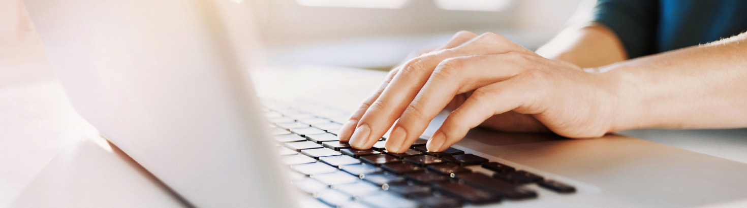 Image of a woman with her hands on the keyboard of a laptop.