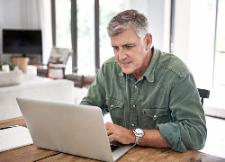 A mature man in is home sits at the counter and looks at his laptop.